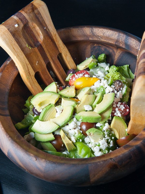 Greens, Kalamata olives, avocado, grape tomatoes, cucumber, bell pepper, purple onion and Feta cheese are combined with a light Greek vinaigrette to make this yummy Greek style salad a winner!