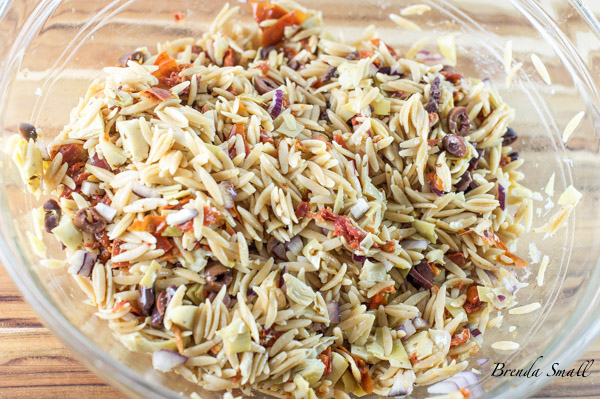 After the Orzo is tossed with the sun-dried tomatoes, artichoke hearts and the Kalamata ollives.